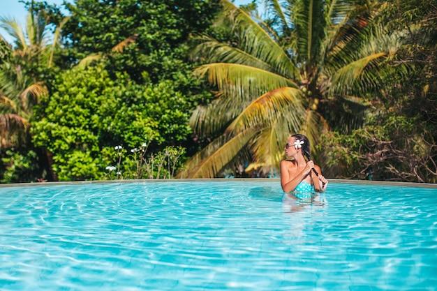 Belle jeune femme se détendre dans la piscine