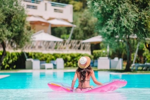Belle jeune femme se détendre dans la piscine.