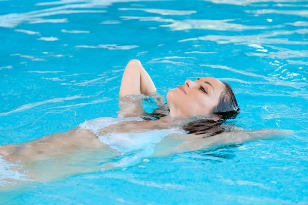Belle jeune femme se détendre sur l'eau à la piscine