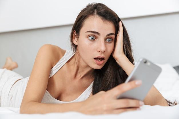 Belle jeune femme se détendre sur le lit à la maison, à l'aide de téléphone mobile