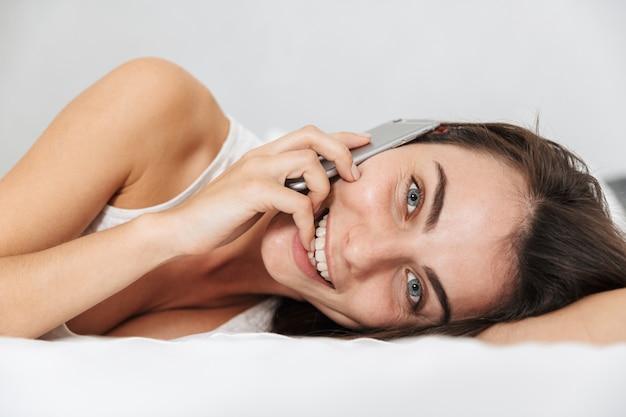 Belle jeune femme se détendre sur le lit à la maison, parler au téléphone mobile