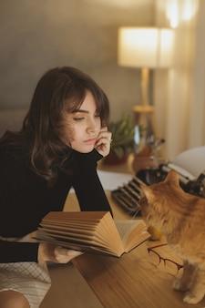 Belle jeune femme se détendre à la maison avec chat dans la soirée confortable et livre de lecture.
