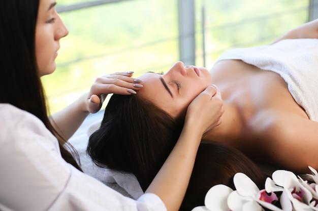 Belle jeune femme se détendre pendant un massage thaï traditionnel au spa et centre de bien-être