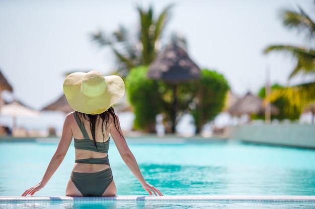 Belle jeune femme se détendre près de la piscine