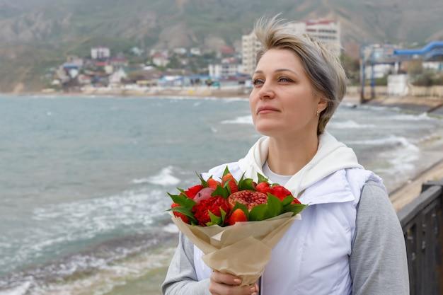 Belle jeune femme se dresse au bord de la mer avec un bouquet dans ses mains