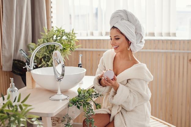 Belle jeune femme se maquille dans la salle de bain