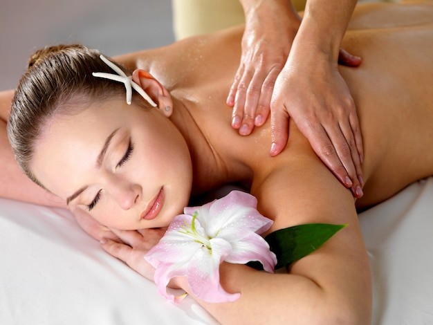 Belle jeune femme se massage relaxant des épaules dans un salon de beauté - à l'intérieur