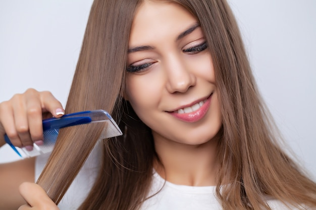 Belle jeune femme se peignant les cheveux dans le salon.