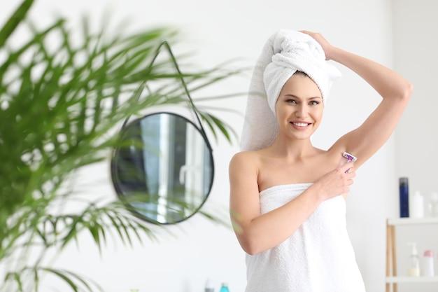 Belle jeune femme se raser les aisselles dans la salle de bain