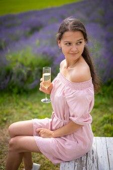 Belle jeune femme se reposant sur un champ de lavande avec le verre de champagne république tchèque