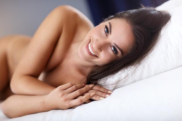 Belle jeune femme se réveillant dans son lit complètement reposée