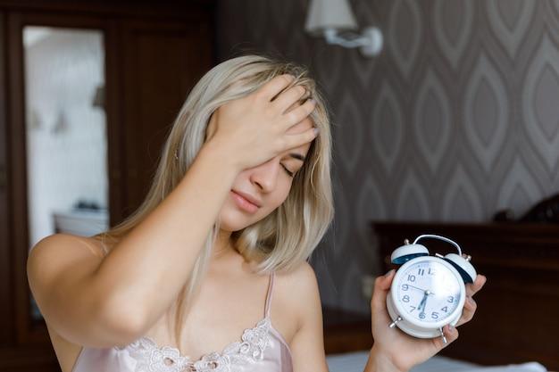 Belle jeune femme se réveille le matin réveil agacé tenant la main, concept de mode de vie.