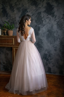 Belle jeune femme se tient dans une délicate robe de mariée contre un mur sombre