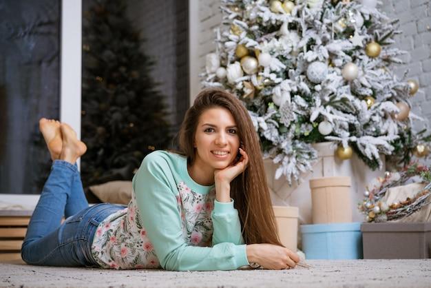 Belle jeune femme se trouve sur le sol près de l'arbre de noël avec des cadeaux