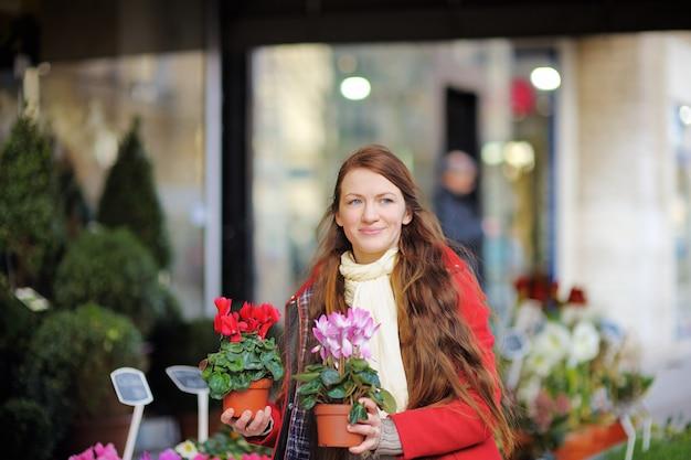 Belle jeune femme en sélectionnant des fleurs fraîches au marché parisien