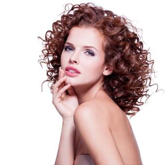 Belle jeune femme sensuelle aux cheveux bouclés brune touchant son visage par les mains sur le mur blanc.