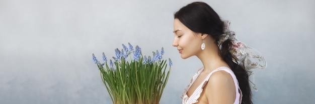 Belle jeune femme sentant le bouquet de fleurs de printemps avec les yeux fermés