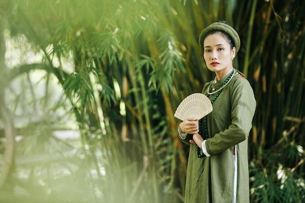 Belle jeune femme sérieuse sérieuse en costume traditionnel vietnamien marchant à l'extérieur avec un ventilateur en bois sculpté
