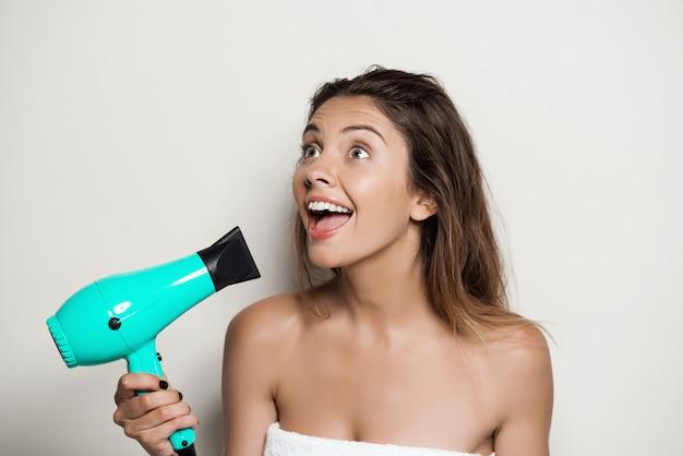 Belle jeune femme en serviette chantant avec sèche-cheveux