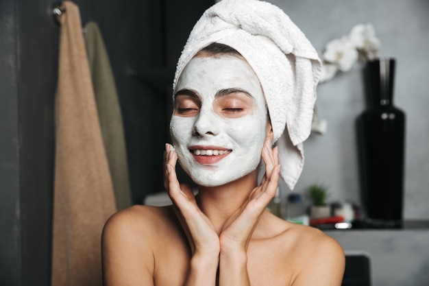 Belle jeune femme avec une serviette enroulée autour de sa tête en appliquant un masque facial dans la salle de bain