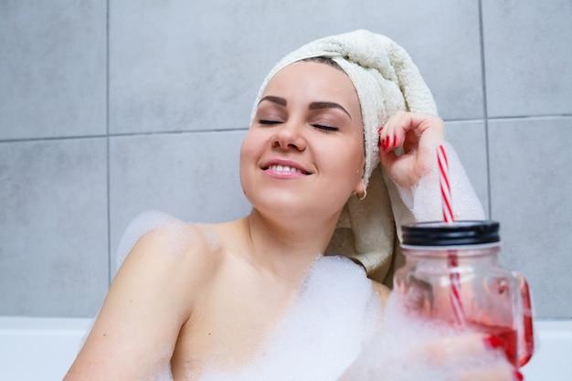 Belle jeune femme avec une serviette sur la tête buvant un cocktail prend un bain à la maison. détendez-vous après une dure journée. le spa est une procédure relaxante.