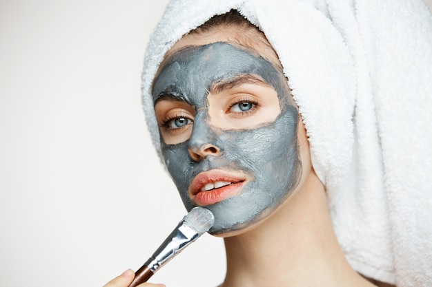 Belle jeune femme en serviette sur la tête couvrant le visage avec un masque souriant. cosmétologie de beauté et spa.