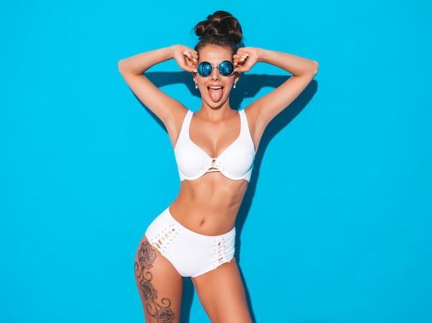 Belle jeune femme sexy avec une coiffure de goule. fille à la mode en maillot de bain blanc d'été décontracté dans des lunettes de soleil. modèle chaud isolé sur bleu. montre la langue
