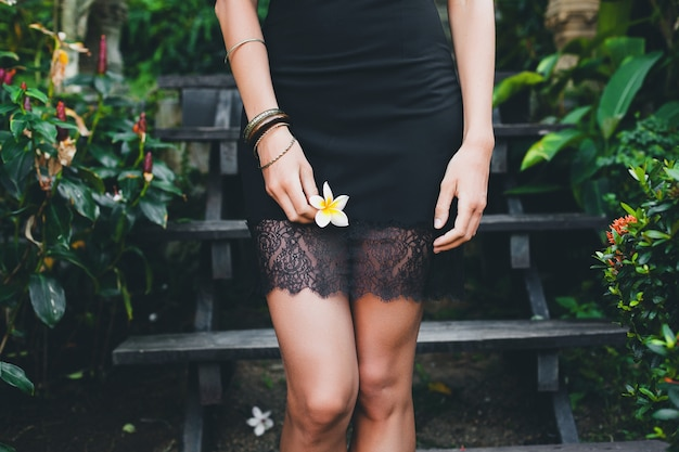 Belle jeune femme sexy dans un jardin tropical, vacances d'été en thaïlande, corps bronzé maigre mince, petite robe noire avec de la dentelle, sensuelle, détendue, tenant la fleur à la main, gros plan des détails