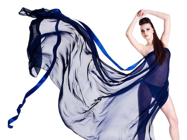 Belle jeune femme sexy en mousseline de soie bleue - isolée sur un mur blanc. portrait complet