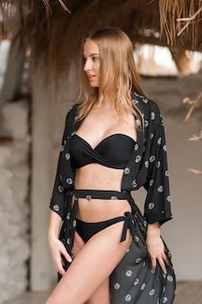 Belle jeune femme sexy avec une silhouette gracieuse sur la plage