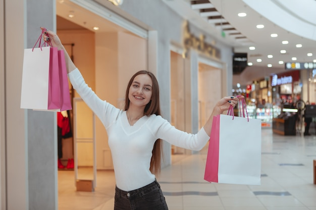 Belle jeune femme shopping au centre commercial local