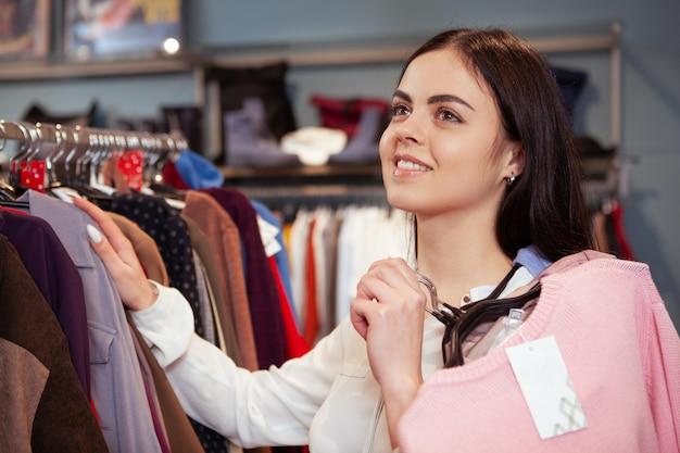 Belle jeune femme shopping au magasin de vêtements