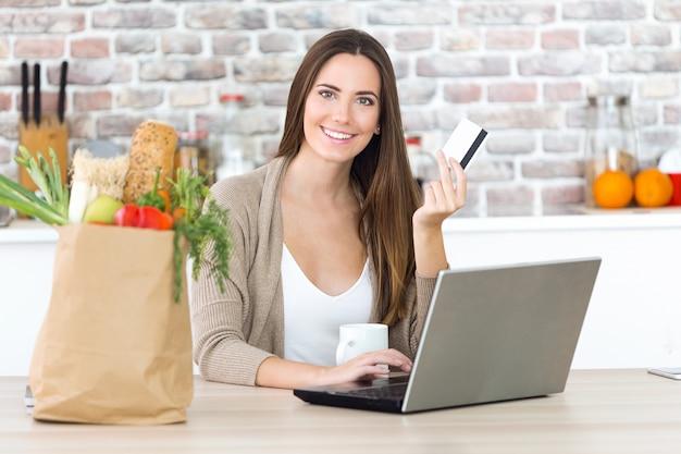 Belle jeune femme shopping avec sa carte en ligne dans la cuisine.