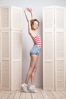 Belle jeune femme en short et haut à rayures posant devant une jalousie