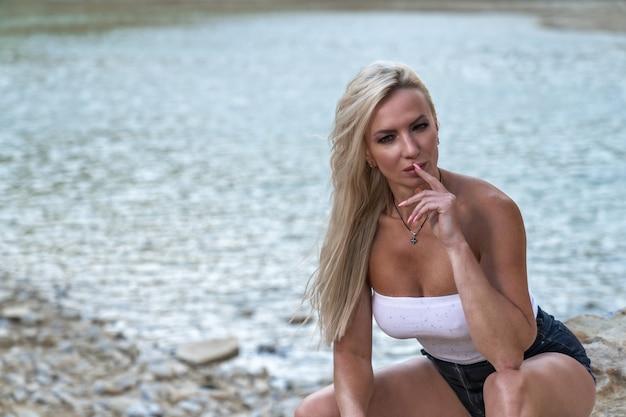 Belle jeune femme en short et un t-shirt est assis sur ses hanches sur le fond du lac