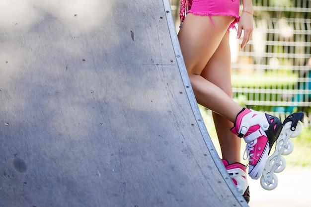 Belle jeune femme en short, t-shirt, lunettes de soleil et patins à roulettes assis sur le banc de béton de la patinoire extérieure.