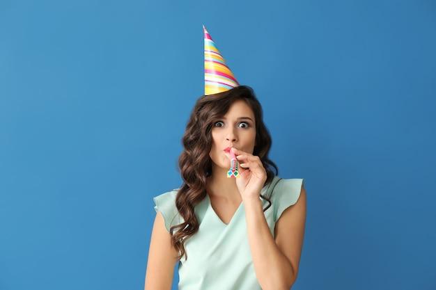 Belle jeune femme avec sifflet de fête et casquette sur fond de couleur