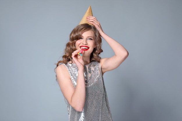 Belle jeune femme avec sifflet de fête sur gris