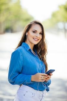 Belle jeune femme avec smartphone en plein air dans la rue. portrait de style de vie