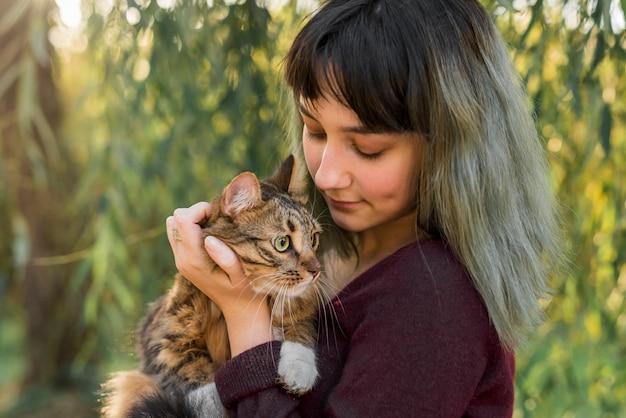 Belle jeune femme avec son beau chat tigré dans le parc