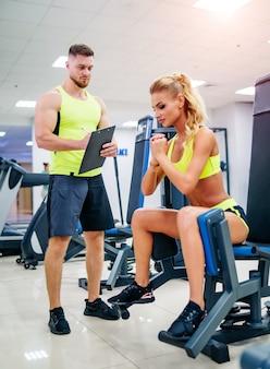Belle jeune femme avec son entraîneur personnel à la salle de sport discuter de ses progrès sur un presse-papiers tenu par l'homme
