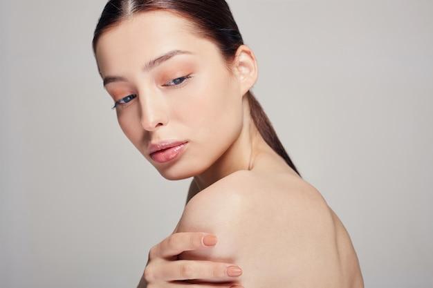 Belle jeune femme sophistiquée aux yeux bleus et lèvres pleines tient une main sur son épaule.