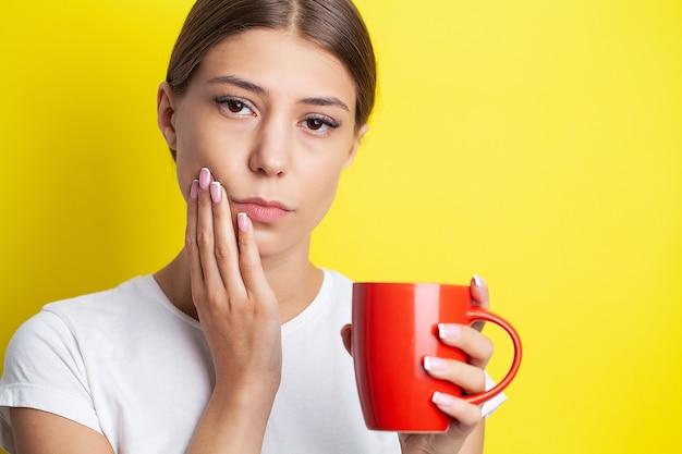 Belle jeune femme souffrant de terribles maux de dents sévères, toucher la joue avec la main