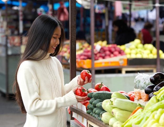 Belle jeune femme souriante au marché aux légumes