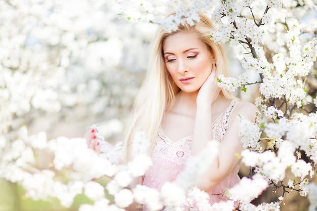 Belle jeune femme souriante blonde en mini robe blanche debout avec des arbres en fleurs à l'arrière-plan