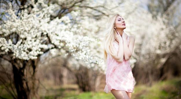 Belle jeune femme souriante blonde en mini robe blanche