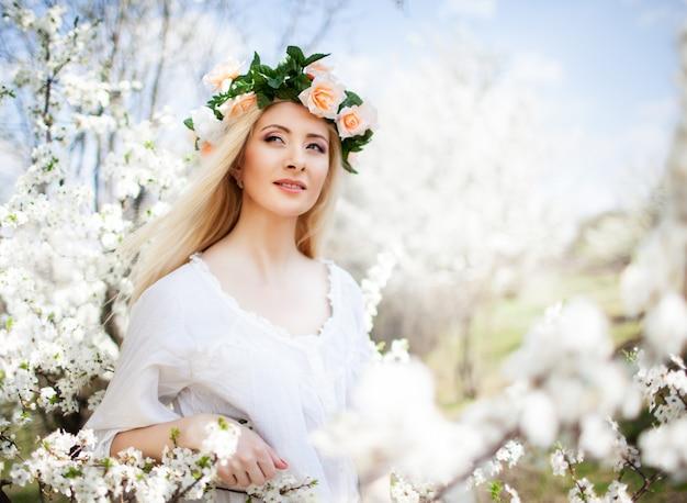 Belle jeune femme souriante blonde en robe blanche et couronne de roses