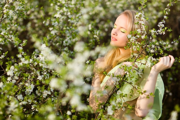 Belle jeune femme souriante blonde en robe jaune debout dans les cerisiers en fleurs et en regardant les fleurs