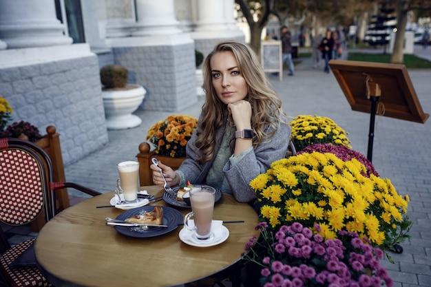 Belle jeune femme souriante et boire du café dans le café en plein air de la rue