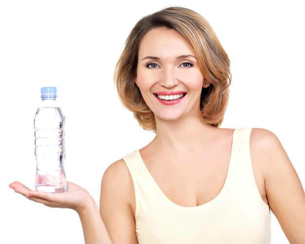 Belle jeune femme souriante avec une bouteille d'eau sur un mur blanc.